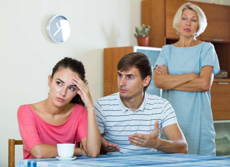 Elderly mother and young man blaming girl in something stock image