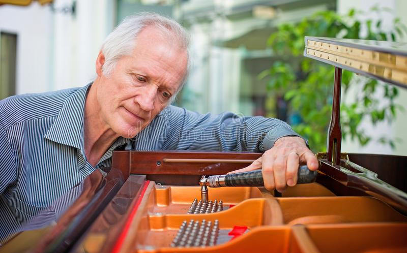Elderly music instrument technician tuning a piano keyboard. stock image