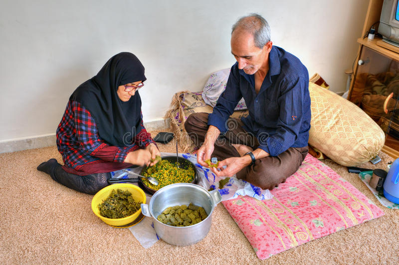 An elderly muslim couple is cooking food at home. royalty free stock image