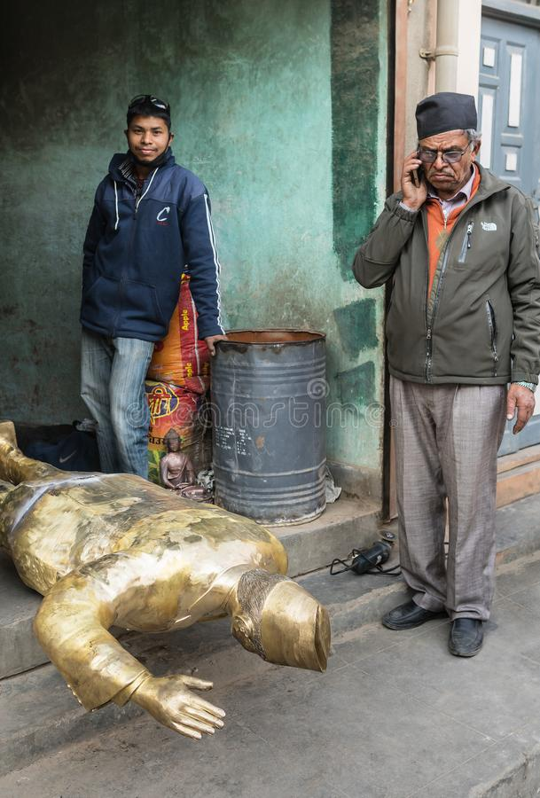 The elderly Nepalese beside his the bronze sculpture. The elderly resident of Nepal costs beside his the brass sculpture lying facedown and with the hand raised royalty free stock photography