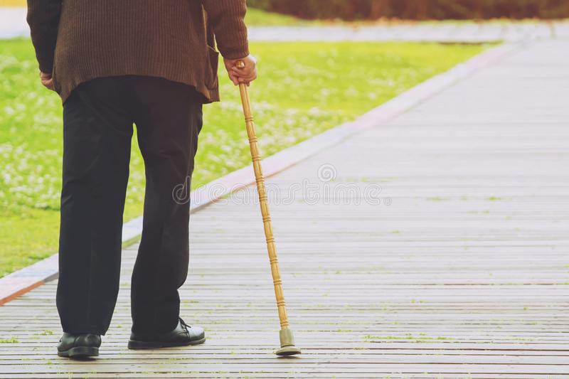 Elderly old man with walking stick stand waiting on footpath sidewalk crossing stock images