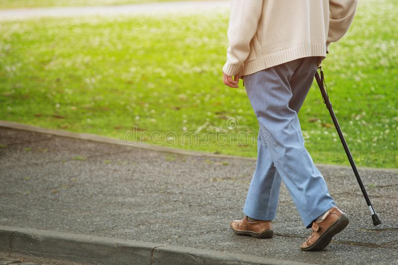 Elderly old man with walking stick stand waiting on footpath sidewalk crossing the street alone. Concept senior across the street to zebra crosswalk royalty free stock images