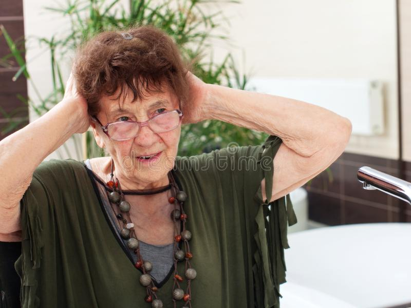 Elderly old woman with a mirror. Mature female at home stock images