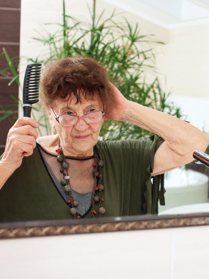 Elderly old woman with a mirror. Mature female at home stock photos