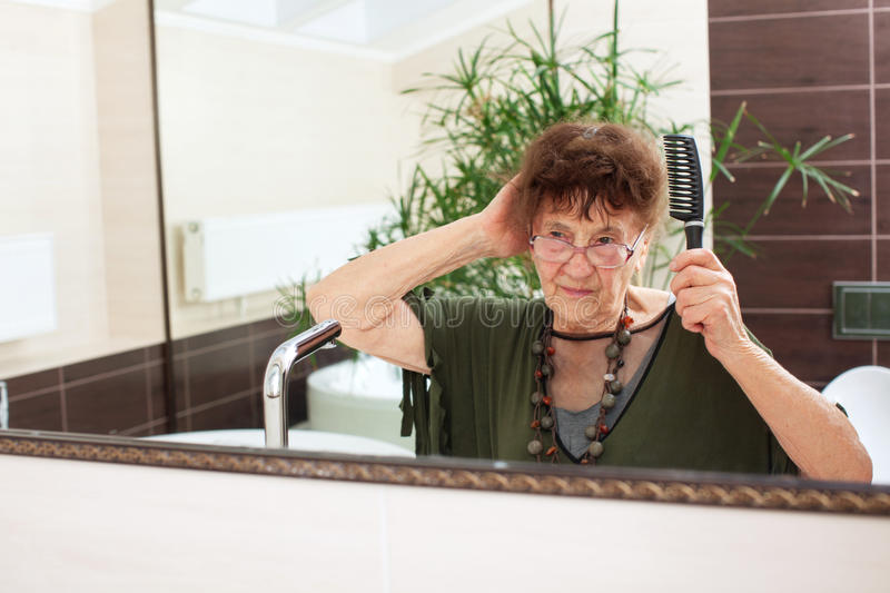 Elderly old woman with a mirror. Mature female at home royalty free stock image