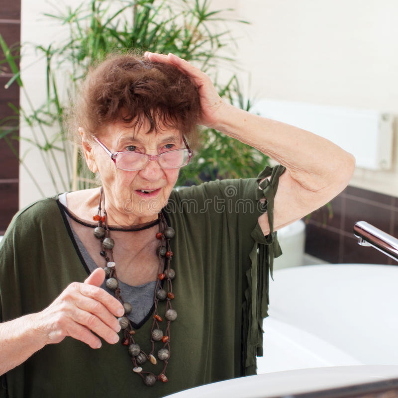 Elderly old woman with a mirror. Mature female at home stock photo
