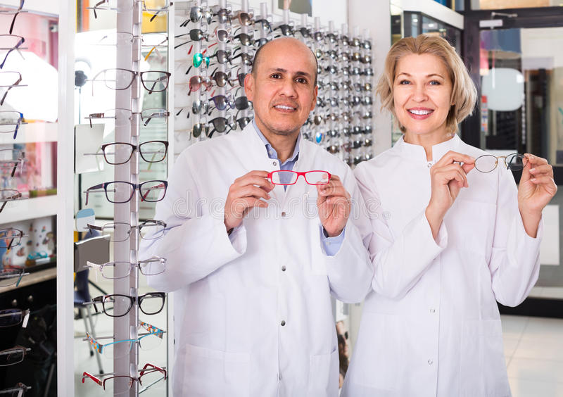Elderly opticians helping to choose glasses in modern optics store. Happy elderly opticians helping to choose glasses in modern optics store royalty free stock photo