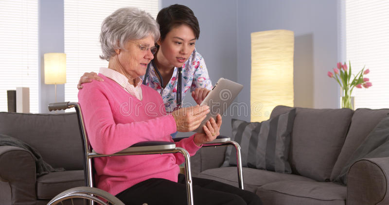 Elderly patient and Asian nurse having fun with tablet royalty free stock photography