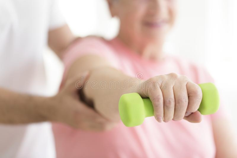 Elderly patient holding minor dumb-bell stock photos