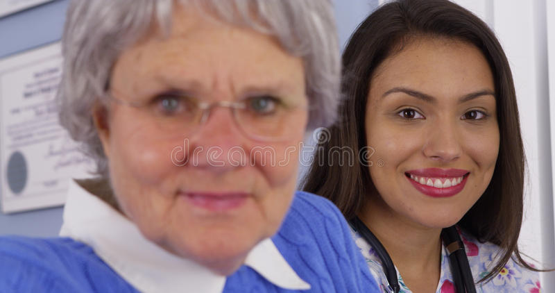 Elderly patient smiling with Mexican caregiver stock image