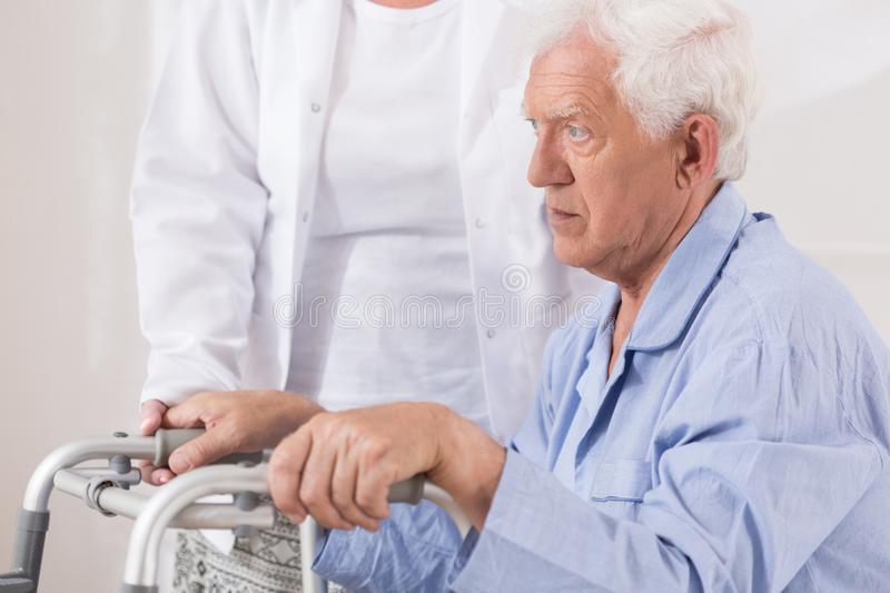 Elderly patient with walking problem. Close up of sad elderly patient with walking problem royalty free stock image