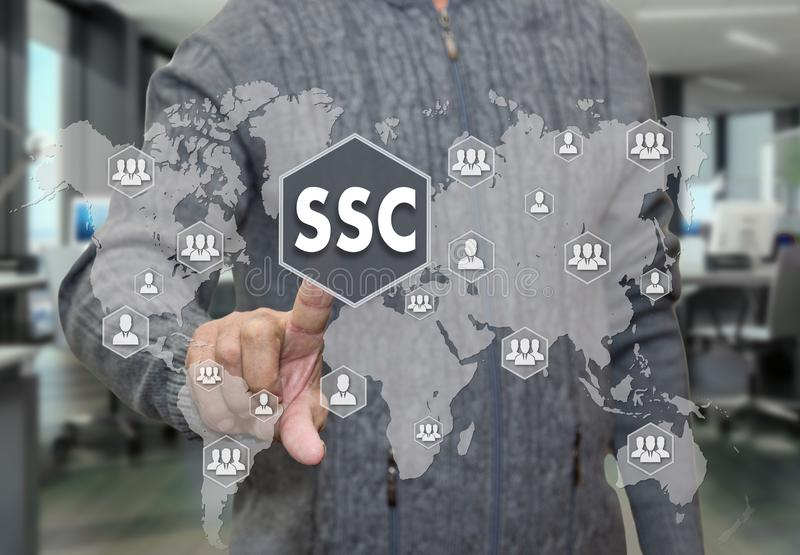An elderly pensioner chooses SSC, service Center around the world on the touch screen on blur office background. stock images