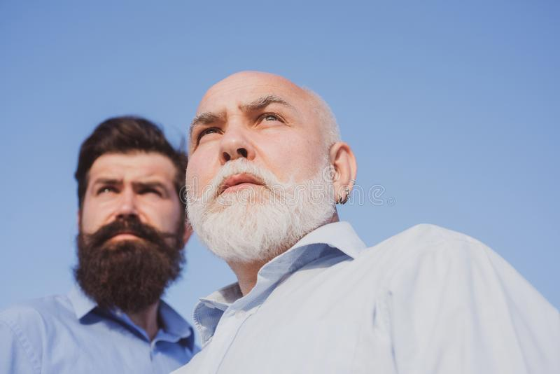 Elderly pensioner and hipster son. Handsome senior men in blue shirt. Men generation. Aged father. Family tradition. Man stock image