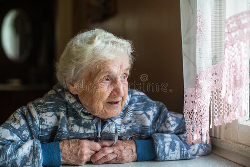 Elderly pensioner woman looks out the window. stock image