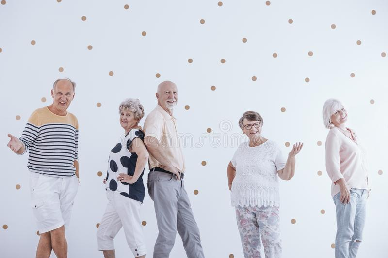 Elderly people celebrating new year`s eve against white wall wit royalty free stock photography