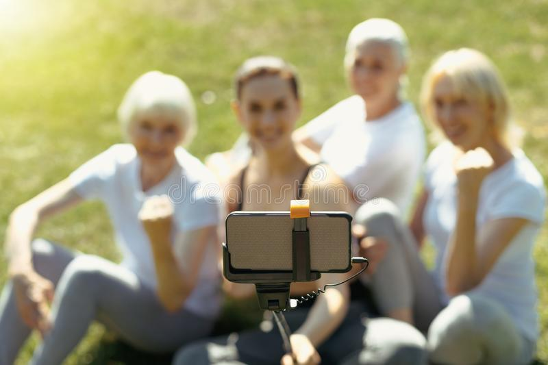 Elderly people and coach posing for selfie outdoors stock photo