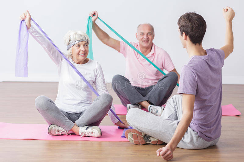 Elderly people do physical exercises stock images