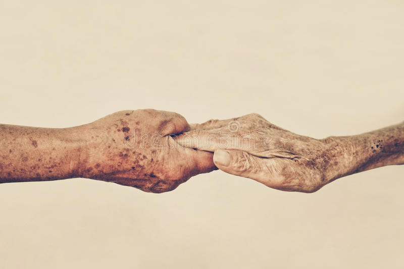 Elderly people holding hands together stock photography