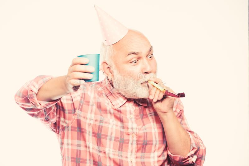 Elderly people. Man bearded grandpa with birthday cap and drink cup. Birthday crazy party. Ideas seniors birthday. Celebrations. Grandfather graybeard blowing royalty free stock images