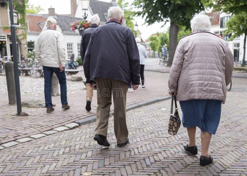 Elderly people on old street in dutch town of amersfoort. Amersfoort, netherlands, 15 june 2019: seniors on old street in dutch town of amersfoort in the stock image