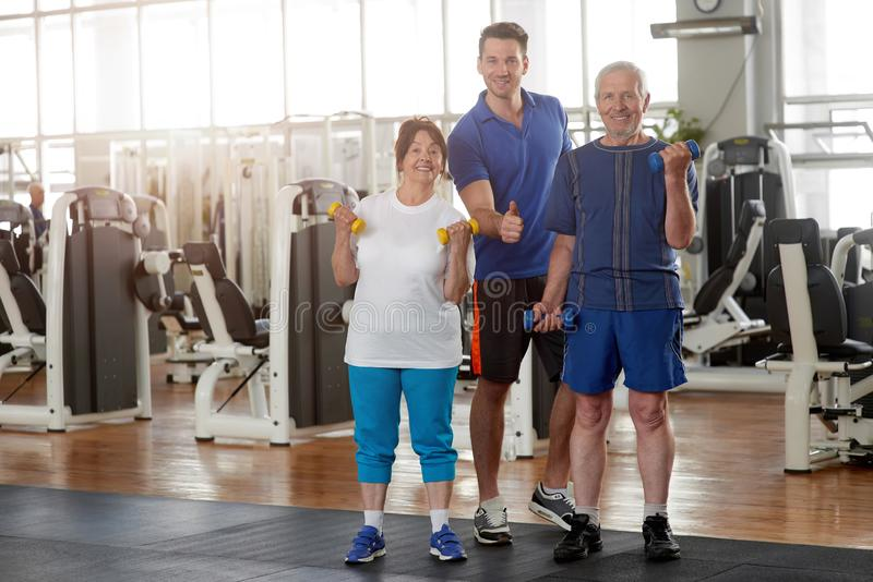 Elderly people with personal trainer at gym. royalty free stock photos