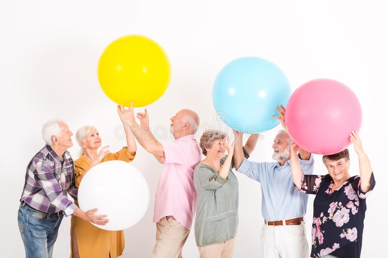Elderly people playing with big balls in room stock image