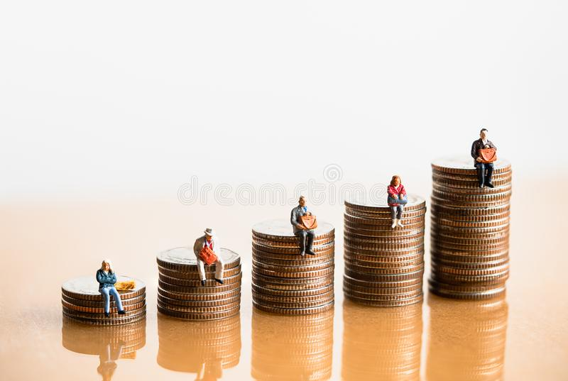 Elderly people sitting on coins stack. stock images