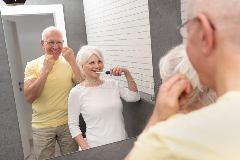 Senior Woman Brushing Teeth Bathroom Mirror Stock Photo