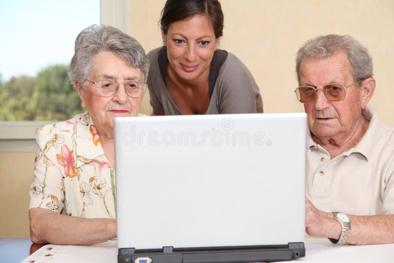 Elderly people using laptop computer royalty free stock photo