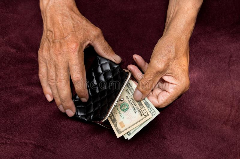 Elderly man puts money in the wallet. royalty free stock image