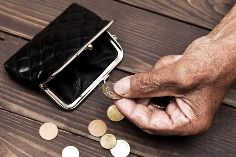 An elderly person holds the coins over the old empty wallet. The. Concept of poverty in retirement. euro hands subsidy cent caucasian billfold save bag british stock photography