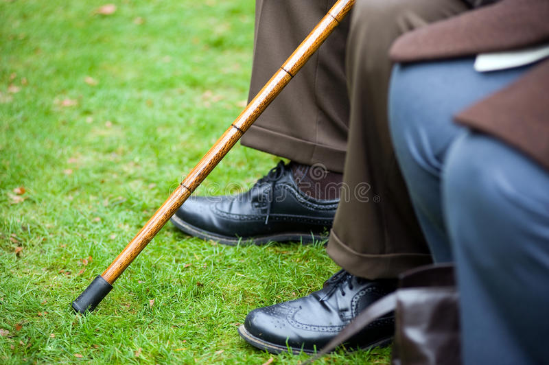Elderly person with stick. An old man sitting with a walking stick in his hand stock photos
