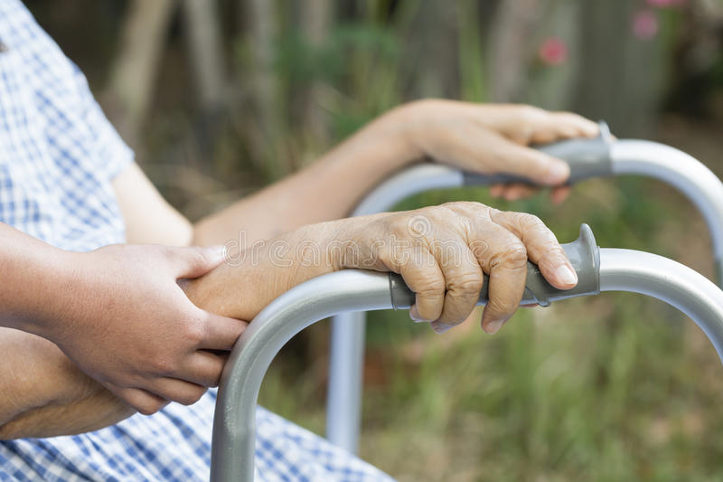 Elderly physical therapy by caregiver in backyard. At home stock photography