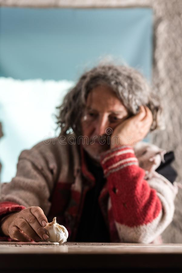 Elderly poor man with dirty hands sitting holding a garlic bulb royalty free stock photography