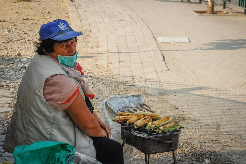 An elderly poor woman sells fried corn on the street of the capital of Albania - Tirana royalty free stock photography