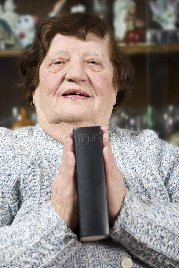 Elderly praying and hold a bible. Elderly woman praying and holding a bible between palms in her home,check also stock photo