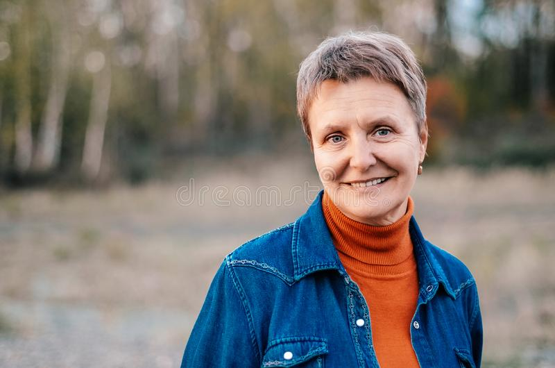 Elderly, pretty smiling woman. Portet outdoors. Concept - happy senior citizen. Elderly pretty smiling woman. Portet outdoors royalty free stock image