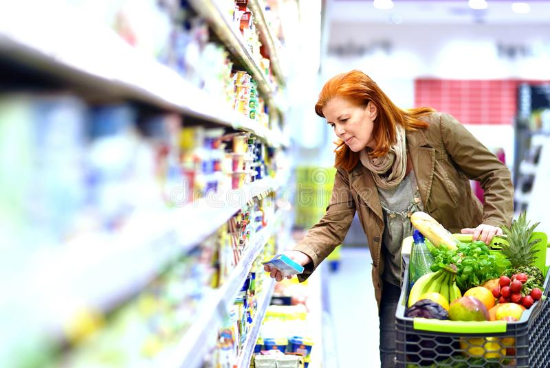 Elderly pretty woman shopping for fresh healthy food in the supermarket royalty free stock photography