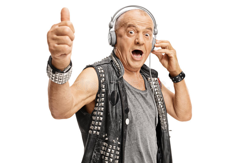 Elderly punker with headphones holding his thumb up royalty free stock image