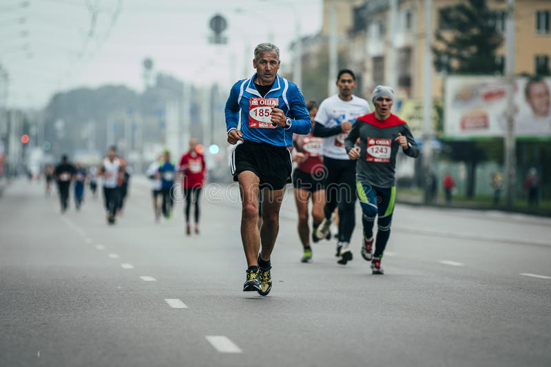 Elderly runner in lead at head group of runners stock photo