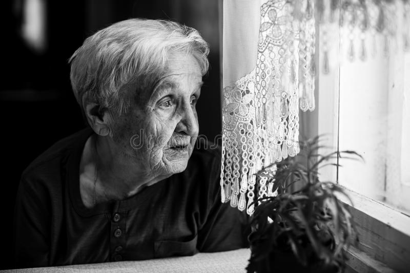 Elderly sad woman looking sad out the window. royalty free stock photo