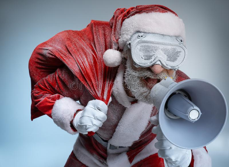 Elderly Santa Claus with sack speaking at megaphone. Mature Santa Claus standing in costume, wearing in frozen protective glasses, speaking at megaphone royalty free stock photography