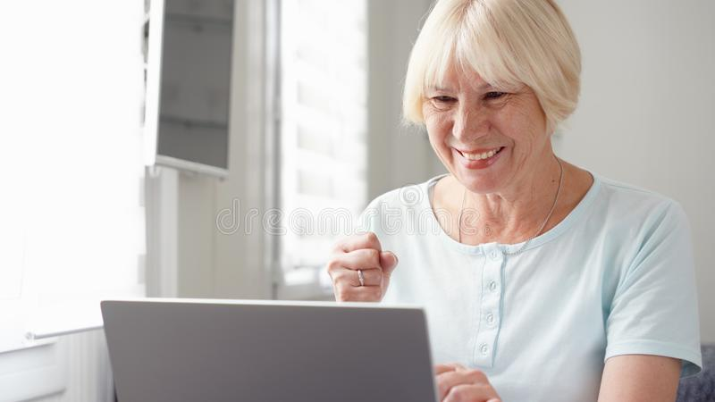 Elderly senior blond woman working on laptop computer at home. Received good news excited and happy. Remote freelance work on retirement, active modern royalty free stock photo
