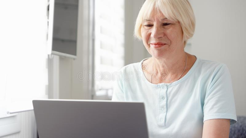 Elderly senior blond woman working on laptop computer at home. Remote freelance work on retirement stock photos