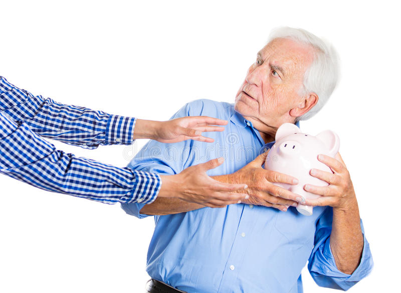Elderly, senior man, grandfather, holding a piggy bank, looking scared, trying to protect his savings from being stolen. A close-up portrait of an elderly royalty free stock image