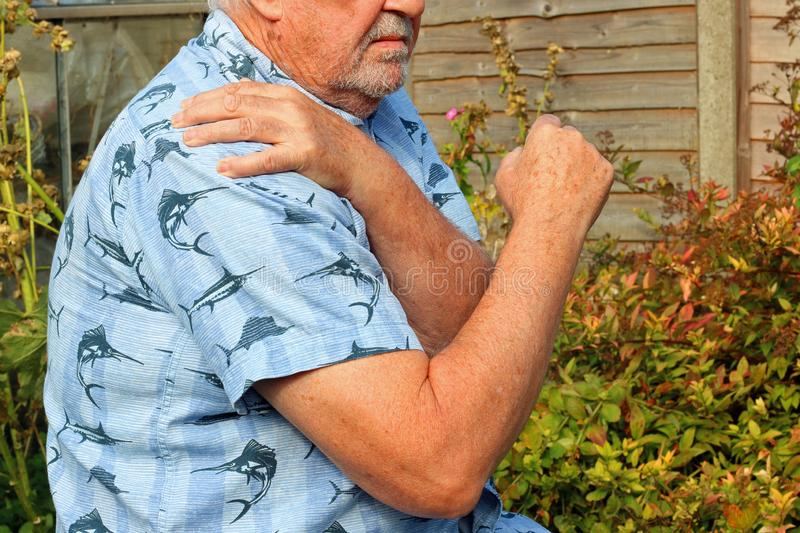 Shoulder pain. Arthritis. Senior in pain. Elderly or senior man holding his shoulder because of pains. Arthritis in his joints stock image