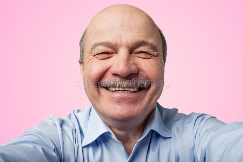 Elderly senior man with a mustache holding a smartphone and makes selfie royalty free stock photo