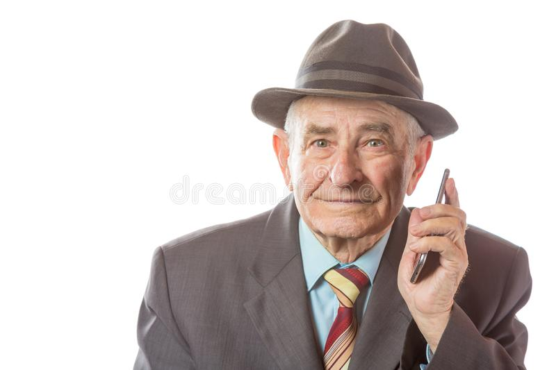 Elderly senior old man with a retro hat talking on mobile phone isolated on white background stock photos