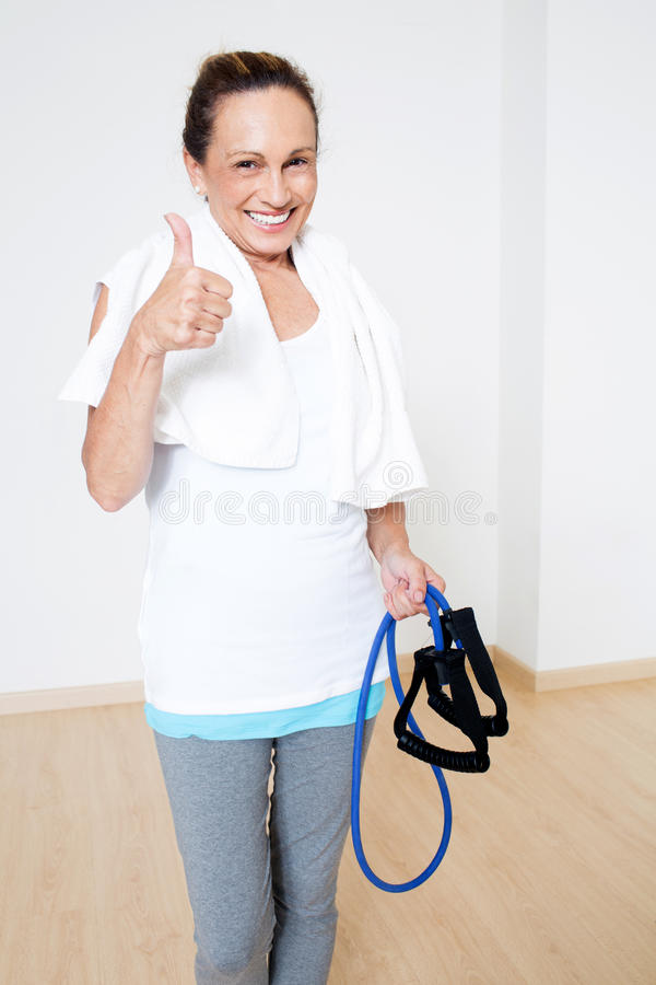 Elderly senior with skipping rope and thumb up. Elderly senior woman in gym with skipping rope and thumb up royalty free stock images