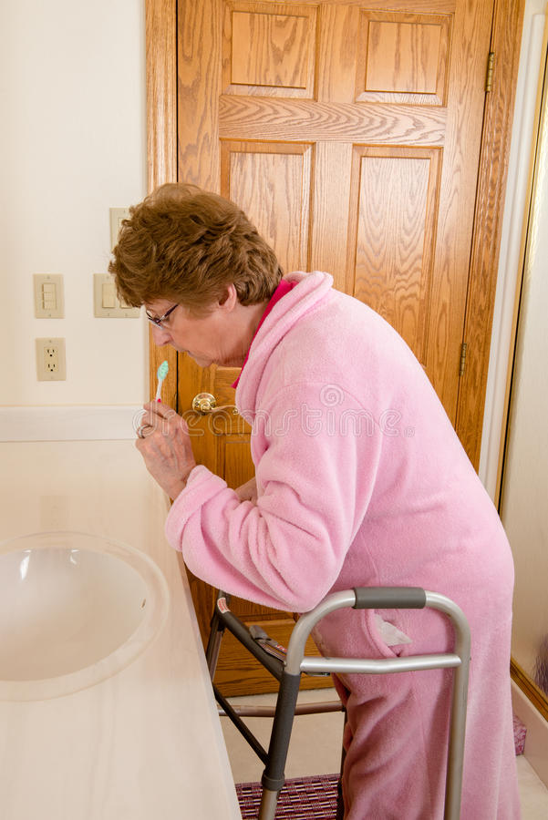 Elderly Senior Woman Brushing Teeth. An elderly senior woman with her medical aid walker is brushing her teeth in a bathroom. Assisted living or nursing home royalty free stock photography